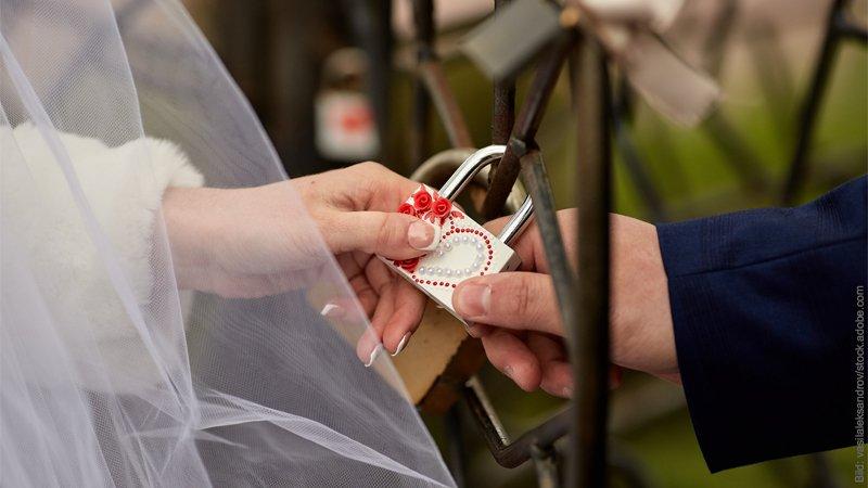 Rituale in der Therapie. Hochzeitspaar bringt ein Schloß an einem Brückengeländer an.
