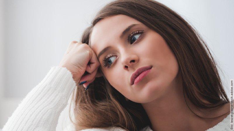 Bist du Burnout gefährdet? Junge Frau stützt erschöpft ihren Kopf auf ihre Hand.