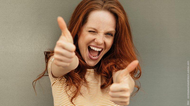 Flirten ohne Stress. Junge Frau lacht über das ganze Gesicht und hält ihre Daumen hoch.
