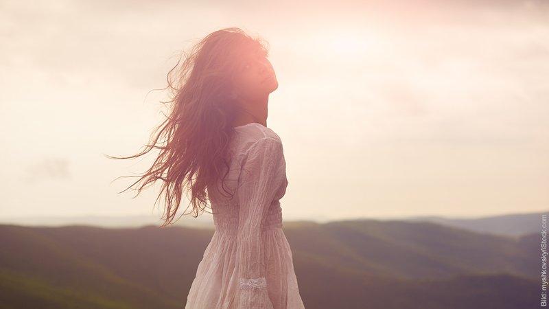 Wie du das Verhalten von deinem Mann veränderst. Verführerische junge Frau mit wilden Haaren lächelt über ihre Schulter zurück.