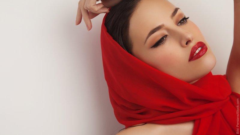 Diva oder Zicke? Frau mit roten Lippen und rotem Tuch um den Kopf lehnt sich lasziv zurück.
