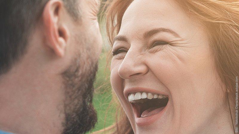Flirten - worauf es ankommt beim Flirt. Frau lacht Mann herzlich an.
