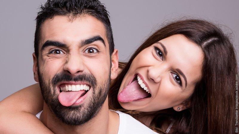 Experiment: glückliche Paare. Mann und Frau strecken fröhlich die Zungen heraus.