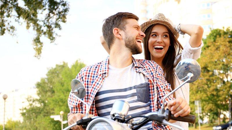Flirten - in wen wir uns verlieben. Junges Paar unterhält sich, schaut sich verliebt an und sitzt auf einem Motorroller.