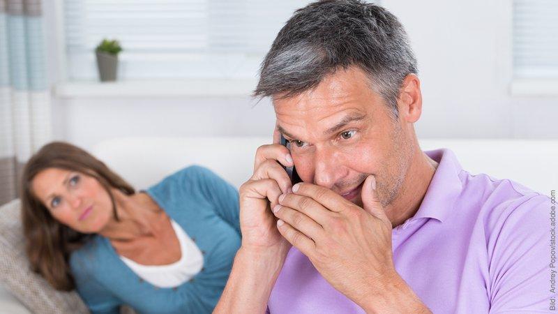Eifersucht und Selbstwert. Mann und Frau. Er telefoniert heimlich, sie schaut skeptisch.