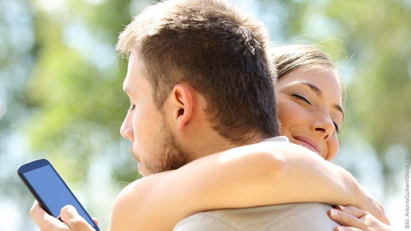 Gefahr für die Beziehung durch das Internet. Mann und Frau umarmen sich. Er schaut hinter dem Rücken der Frau heimlich in sein Handy.