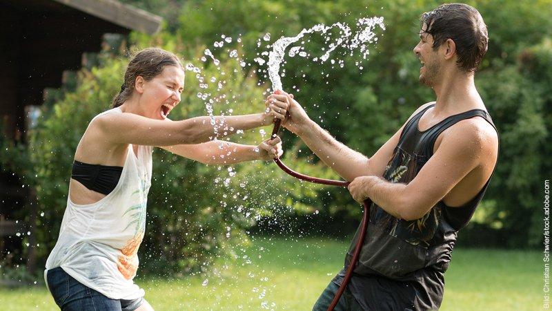 Ist der Mensch überhaupt für eine Partnerschaft gebaut? Junges Paar kämpft um den Gartenschlauch und spritzt sich dabei komplett nass. Beide lachen.