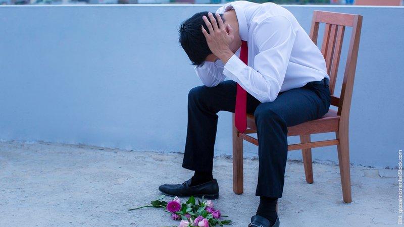 Warum langjährige Partnerschaften häufig nach der Heirat scheitern. Mann sitzt auf einem Stuhl und stützt den Kopf in seine Hände. Vor ihm auf dem Boden liegen Rosen.