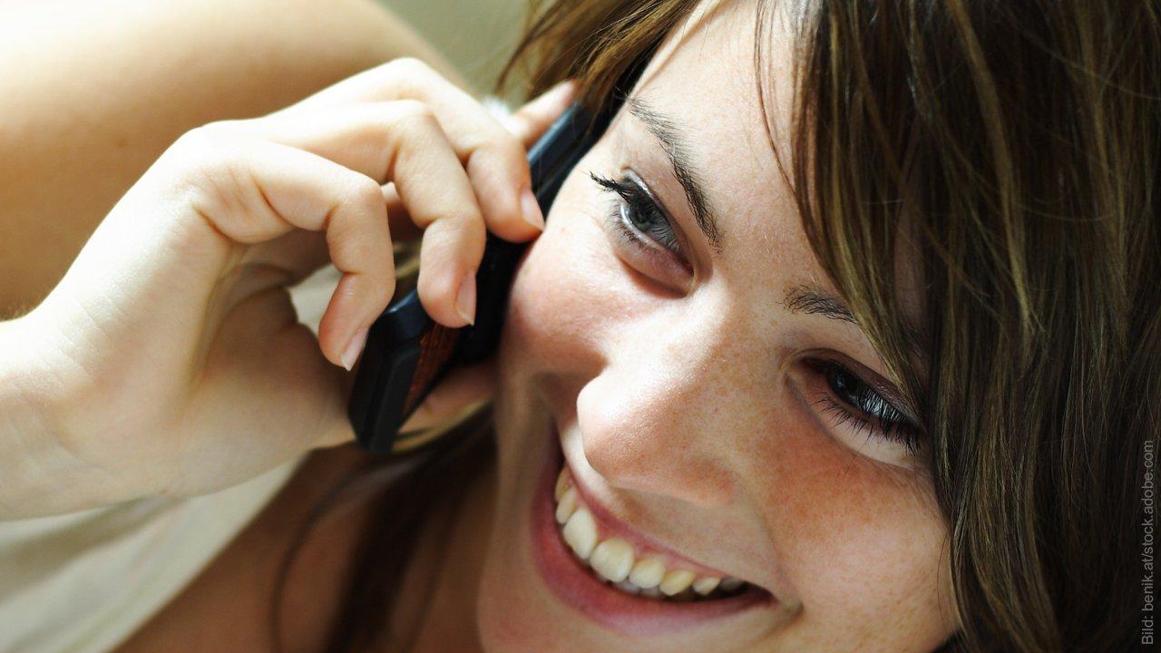 Tipps für Telefonate beim Flirten. Frau lacht ins Telefon.