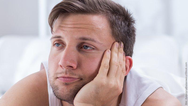 Verflachung der Affekte. Mann stützt den Kopf in die Hand und lässt seinen Blick in die Ferne gleiten, verzeiht dabei sein Gesicht.