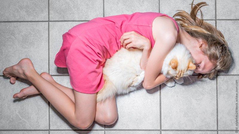 Angst vor Ablehnung durch den Partner. Frau liegt auf kahlen Fließen und klammert sich an eine Katze.