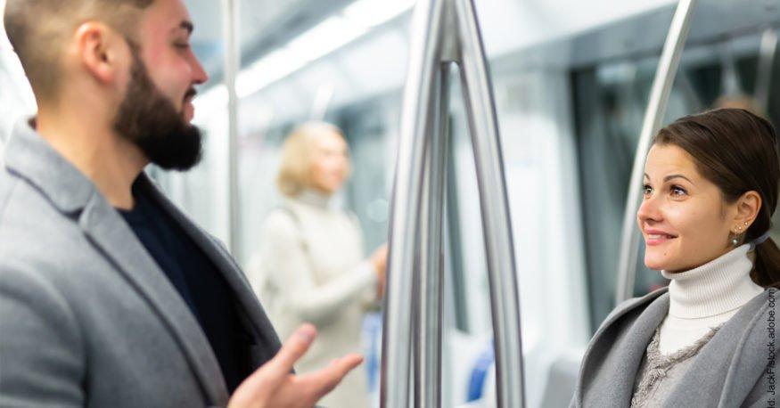 Kürzeste Flirt Anleitung für Männer. Mann flirtet in einem öffentlichen Verkehrsmittel mit einer Frau.