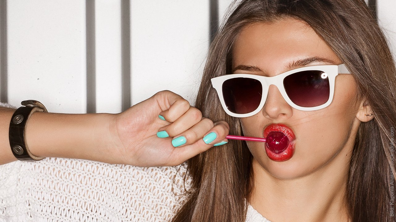 Was beeinflusst das Selbstwertgefühl: 4 Faktoren: Junge Frau mit roten Lippen lutscht einen Lolli.