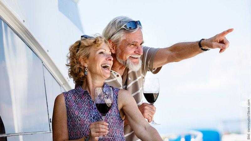 Verwechslung von Wunsch und Ziel. Mann zeigt mit ausgestrecktem Arm seiner Frau etwas. Es ist ein älteres Paar, sie halten ein Glas Rotwein in der Hand.