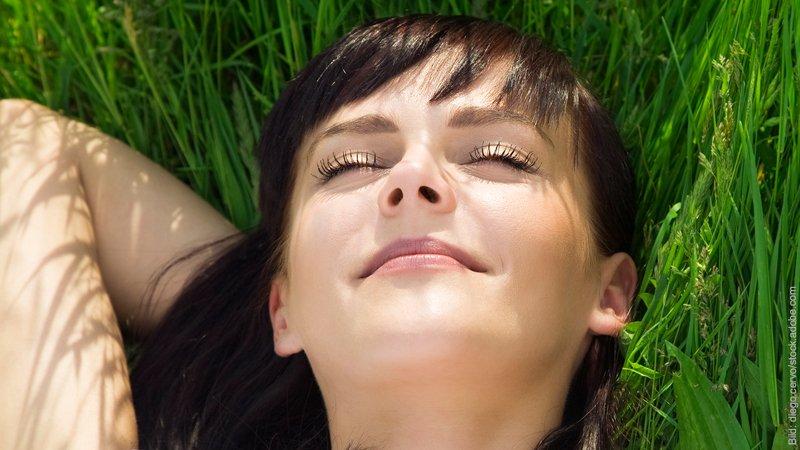 Was passiert in Hypnose? Frau liegt mit geschlossenen Augen und entspannt auf einer Wiese.