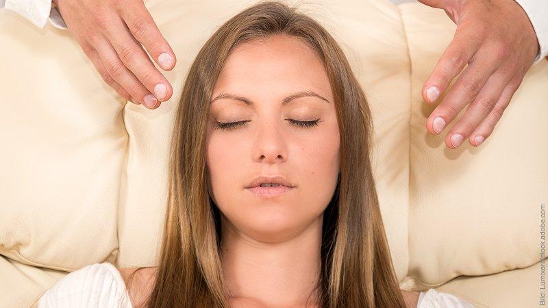 Liebeskummer überwinden mit Hypnose - geht das? Frau liegt mit geschlossenen Augen entspannt da.
