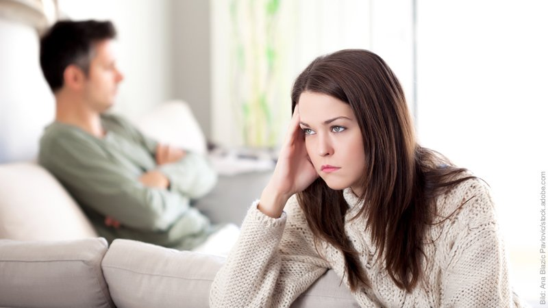 Hypnose gegen Liebeskummer. Frau schaut traurig, sie sitzt auf ihrem Bett.