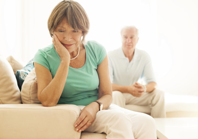 Senior woman upset while husband watches