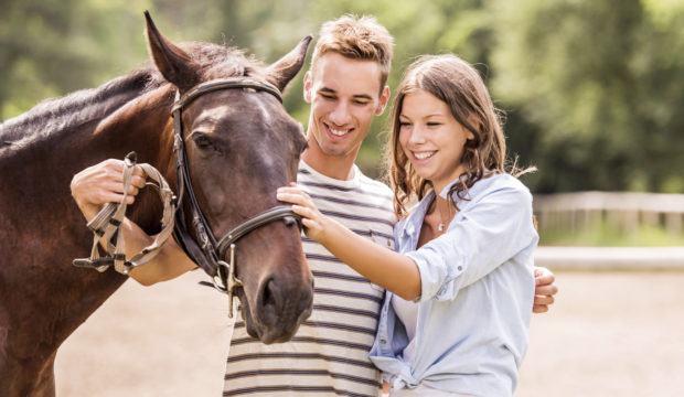 Young happy couple enjoying with their horse outdoors.