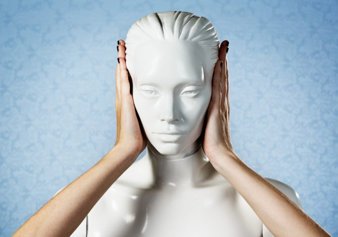 """Real, feminine hands cover the ears of a plastic mannequin or shop window dummy in the """"hear no evil"""" gesture, Copy space on the pale blue background."""