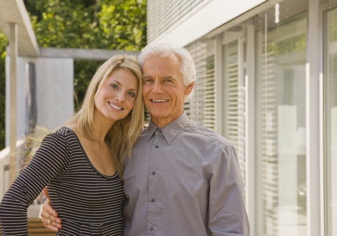 Portrait of a senior man and a young woman embracing each other and smiling
