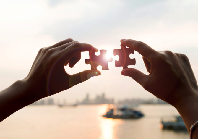 Human hands connecting jigsaw puzzle pieces, teamwork concept.