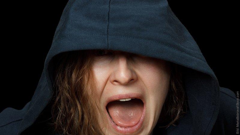 Wenn Eifersucht zur tödlichen Gefahr wird. Frau schreit. Sie trägt einen dunklen Kapuzen-Pullover.