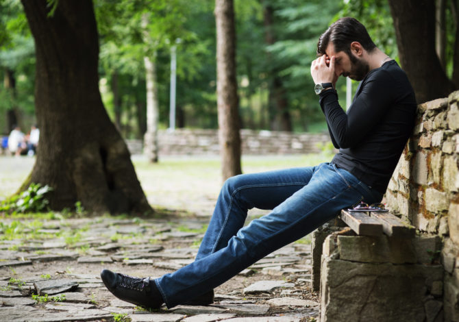 Sad and depressed young man holding head in hands and sitting on a bench in the park
