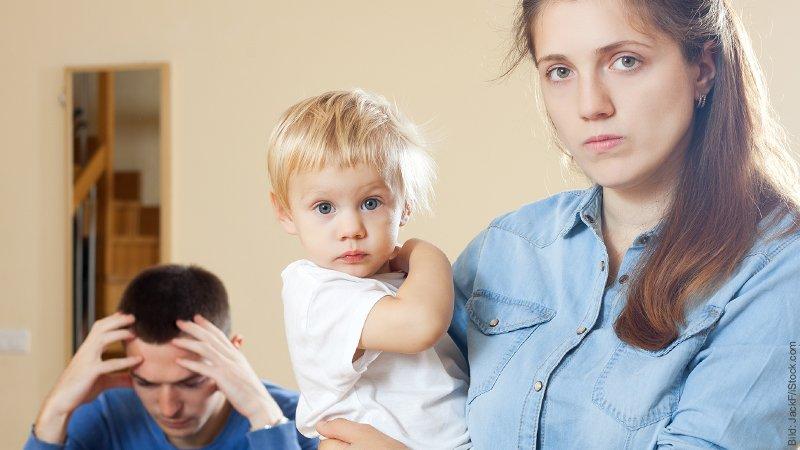 Trennung als Eltern - Wenn das Elternsein die Beziehung überlagert. Traurig schauende Frau trägt Kleinkind auf dem Arm, der Mann stütz den Kopf in die Hände.