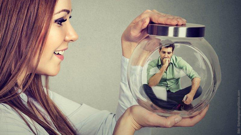 Gleiche Augenhöhe in Partnerschaften. Frau betrachtet ihren Mann, den sie in einem Glas gefangen hält.