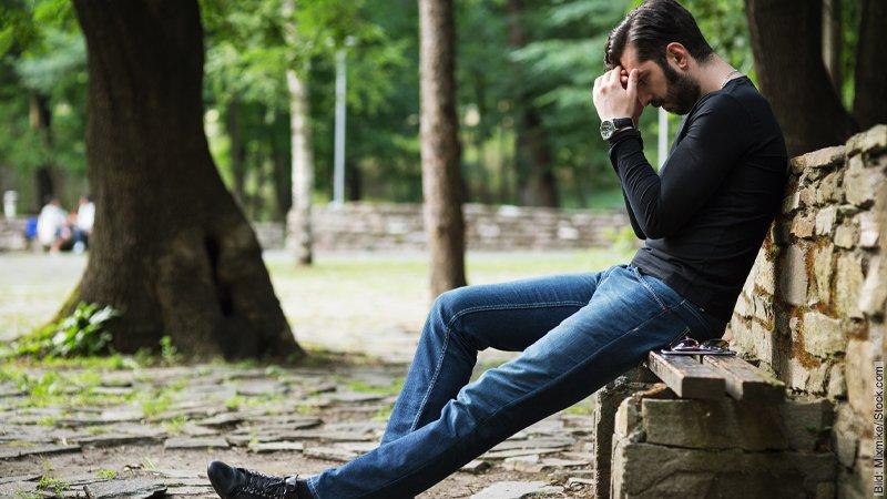 Krise im Urlaub: Überlebt das deine Beziehung? Mann sitzt verzweifelt auf einer Mauer.