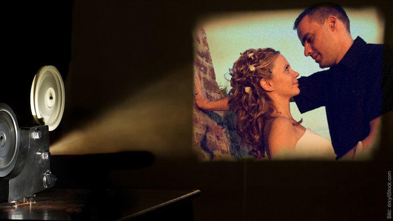 Liebeskummer durch Liebesfilm? Ein Filmprojektor ist links unten zu sehen. Auf der Leinwand ein Paar. Sie hat Blumen in den Haaren und schaut zu ihm auf. Er lehnt lässig maskulin da.