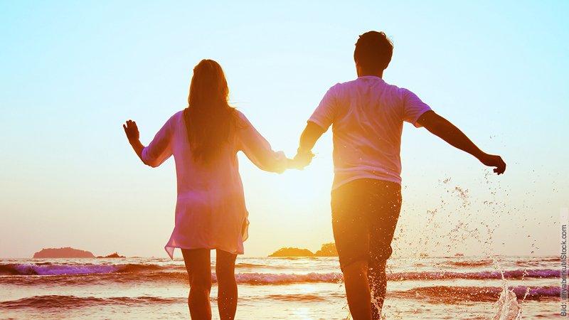 Warum Sie den richtigen Partner nicht finden. Ein Paar hält sich an den Händen und läuft in Richtung Sonnenuntergang am Strand.
