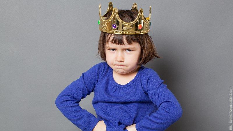 Was ist euer größtes Problem in Bezug auf eure Partnerschaft? Kleines Mädchen mit einer Spielzeugkrone auf dem Kopf schaut trotzig.