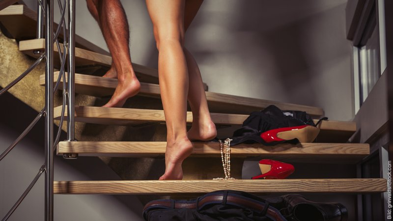 Warum Verliebtheit eine Prüfung ist. Kleider und Schuhe liegen verstreut auf einer Treppe. Man sieht nur die nackten Beine eines Paares, die nach oben gehen.