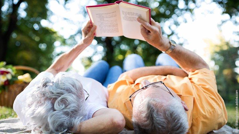 Nähe in Beziehungen - der Nähe Pol. Ein älteres Paar liest in einem Garten gemeinsam in einem Buch.