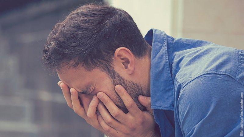 Trennung auf Zeit - gut oder schlecht? Mann stütz sein Gesicht in die Hände. Er sieht traurig aus.