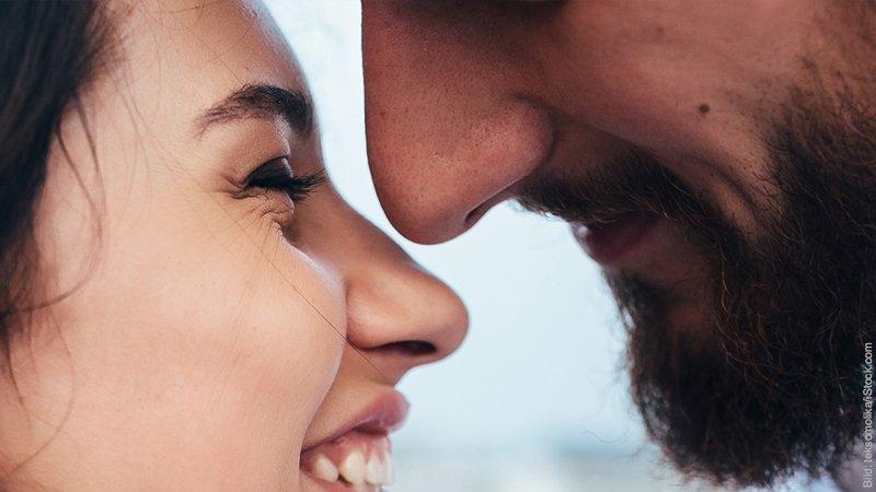 Wie entsteht Partnerschaft? Junge Frau und junger Mann schauen sich zärtlich an, dabei sind ihre Gesichter sich sehr nahe.