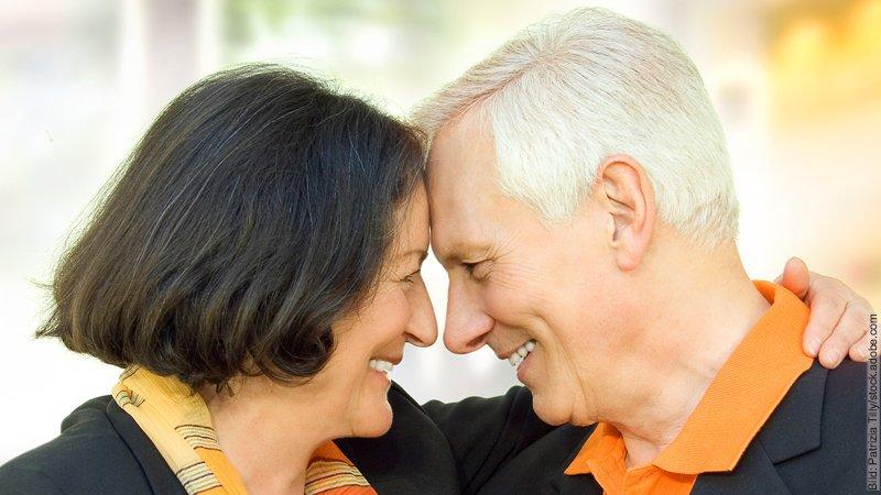 Die Sprachen der Liebe. Ein älteres Paar schaut sich liebevoll an, dabei berühren sie sich Stirn an Stirn.