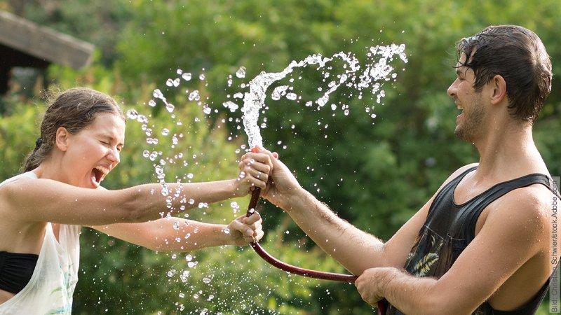 Distanz in Beziehungen – Der Distanz-Pol. Junges Paar neckt sich mit dem Gartenschlauch. Dabei spritze das Wasser um sie herum.