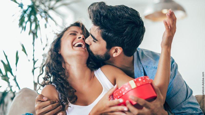 Valentinstag - leider doch nicht doof. Ein Paar freut sich, er küsst sie. Sie hält ein Geschenk in ihren Händen.