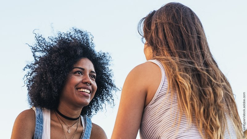Beziehung verbessern durch 7 Power-Fragen. Zwei Frauen unterhalten sich angeregt, die eine hat lange blonde Haare und ist von hintern zu sehen, die andere hat schwarze Locken, lacht und ist von vorn zu sehen.