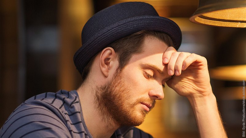 Einsamkeit - alleine einsam sein. Mann mit Hut stützt seinen Kopf auf der Hand ab.