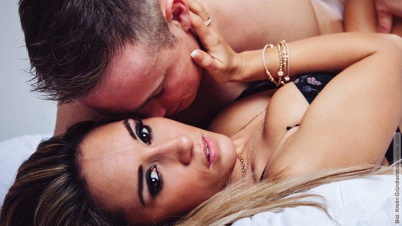 8 unverwechselbare Zeichen für Fremdgehen. Mann und Frau liegend, Mann beugt sich über Frau um sie zu küssen. Beide zeigen viel Haut.