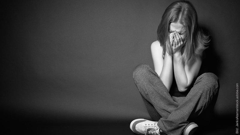 Betrogen worden - 8 Phasen und 11 Tipps. Frau sitzt auf dem Boden und hält ihre Hände vor ihr Gesicht. Sie sieht traurig aus. Schwarz-weiß Foto.