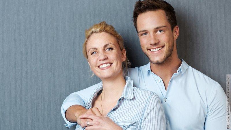 Selbstbewusstsein - attraktiv für die Partnerschaft. Strahlendes Paar. Sie lehnt sich mit ihrem Rücken an seine Brust, er umarmt sie.