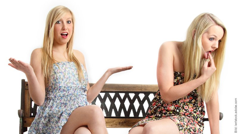 Zickenkrieg - Zielsicher die Seele der Anderen verletzten. Zwei Frauen im Kleidchen sitzen auf einer Bank und zicken sich an.