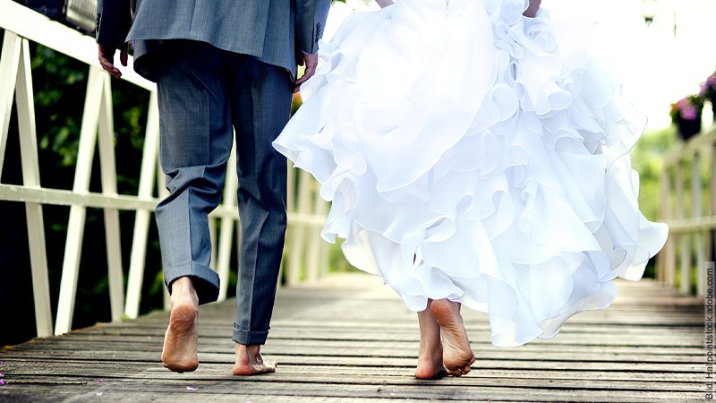 Die perfekte Hochzeit. Hochzeitspaar läuft barfuß auf einem Weg, der aus Planken besteht.