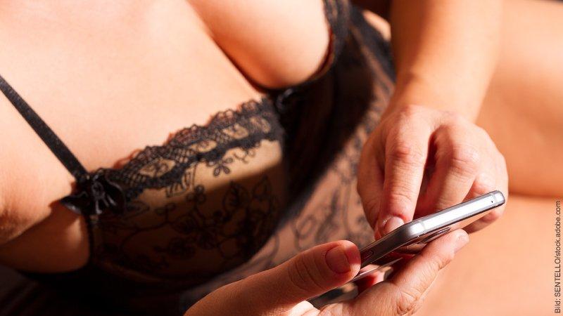 Fernbeziehung Tipps gegen Sehnsucht. Frau in Dessous tippt auf ihrem Handy.