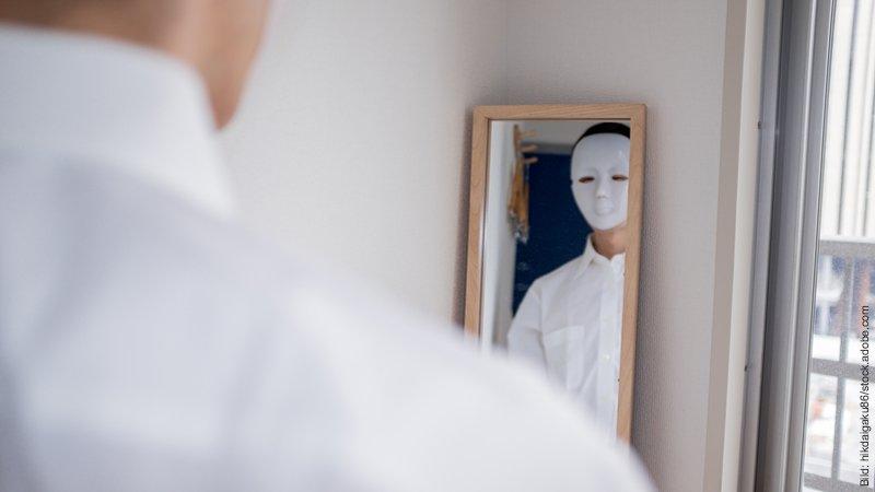 Wenn der Partner lügt - Was tun? Ein Mann mit weißer Maske betrachtet sich im Spiegel.